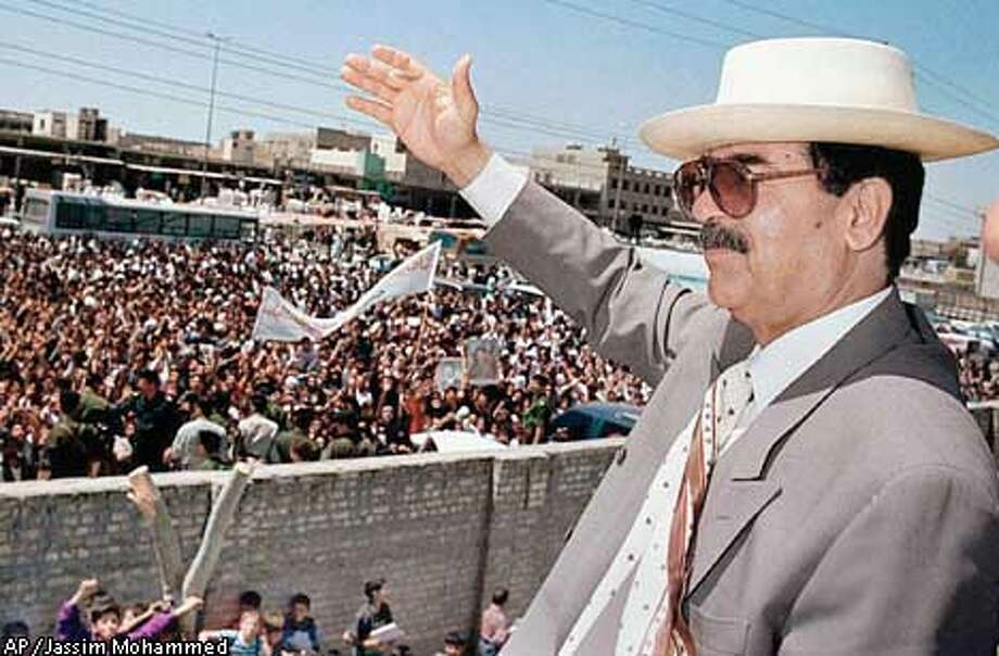 "** FILE ** Iraqi President Saddam Hussein waves to people of Saddam City in Baghdad during his visit in this April 21, 1998, file photo. President Bush and Vice President Dick Cheney call Hussein the ""enemy."" Defense Secretary Donald H. Rumsfeld compares him to Adolf Hitler. In trying persuade the public, U.S. allies and, perhaps, Saddam himself that he is fair game, the Bush administration is ratcheting up its rhetoric. (AP Photo/Jassim Mohammed, File) Photo: JASSIM MOHAMMED"
