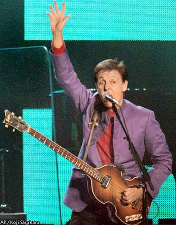 """Paul McCartney performs in front of an estimated 50,000 fans who packed Tokyo Dome in Tokyo, Japan on Monday Nov. 11, 2002. McCartney says he believes the bad press his wife, Heather Mills, has been getting will pass once his fans get used to the couple being married. """"All youve got to do is think back to Linda,"""" McCartney told TV Guide for its Nov. 23, 2002 issue, referring to his first wife, who died of cancer in 1998. (AP Photo/Koji Sasahara) Photo: KOJI SASAHARA"""