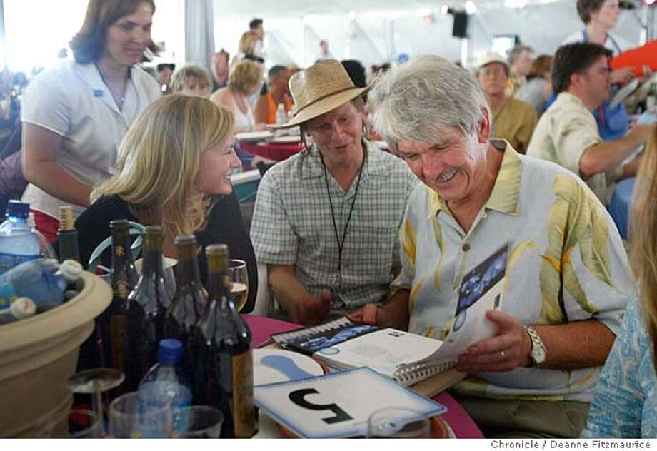 Ron Kuhn (at right) looks at auction catalog after he bids and wins a lot of ZD wines at Napa Valley Vintners Association Wine Auction in St. Helena.  Deanne Fitzmaurice/ The Chronicle Photo: Deanne Fitzmaurice