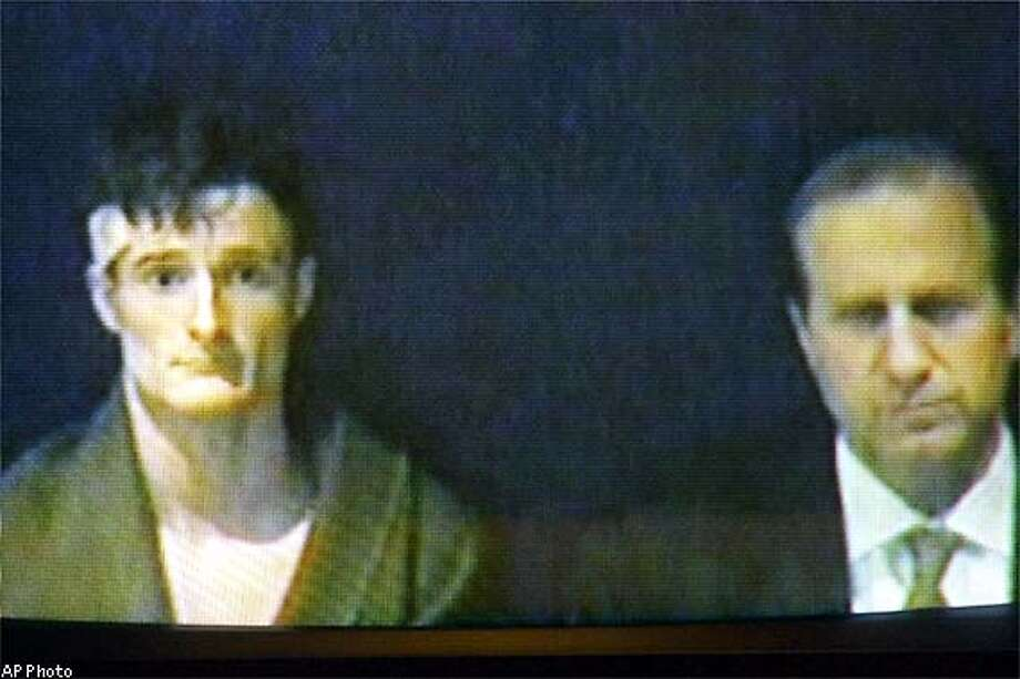 Andrew McCrae, left, of Olympia, Wash., is seen with his lawyer Mark Sisti on a video screen monitor in Concord District Court during his arraignment, Tuesday, Nov. 26, 2002. McCrae is accused of shooting Officer David Mobilio in the head a week ago, while Mobilio was putting gas in his cruiser in Red Bluff, Calif. McCrae was arrested in a hotel in Concord Tuesday. (AP Photo/Jim Cole) Photo: JIM COLE