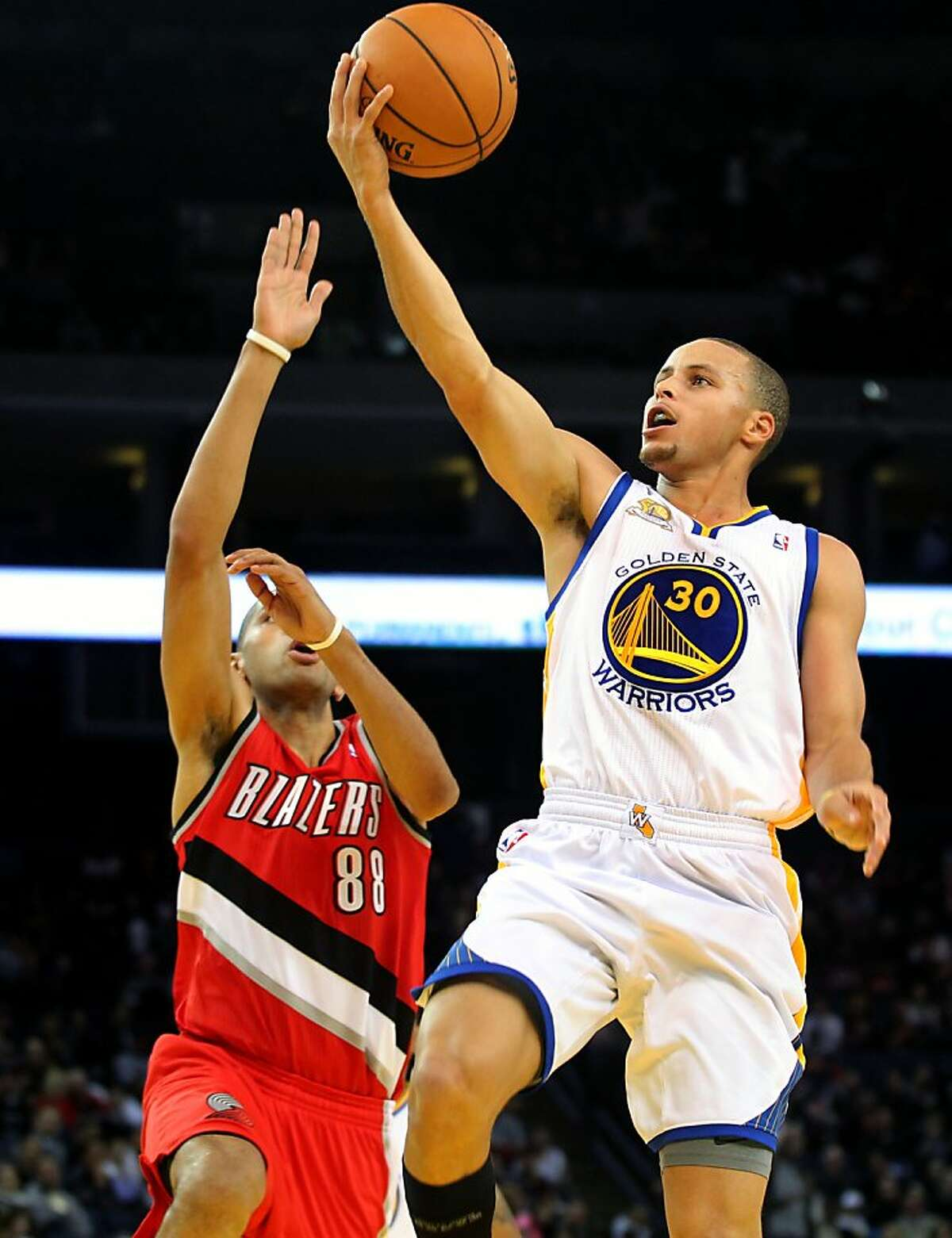 Golden State Warriors' Stephen Curry (30) scores over Portland Trail Blazers Nicolas Batum (88) during the first half of their NBA basketball game in Oakland, Calif., Wednesday, January 25, 2012.