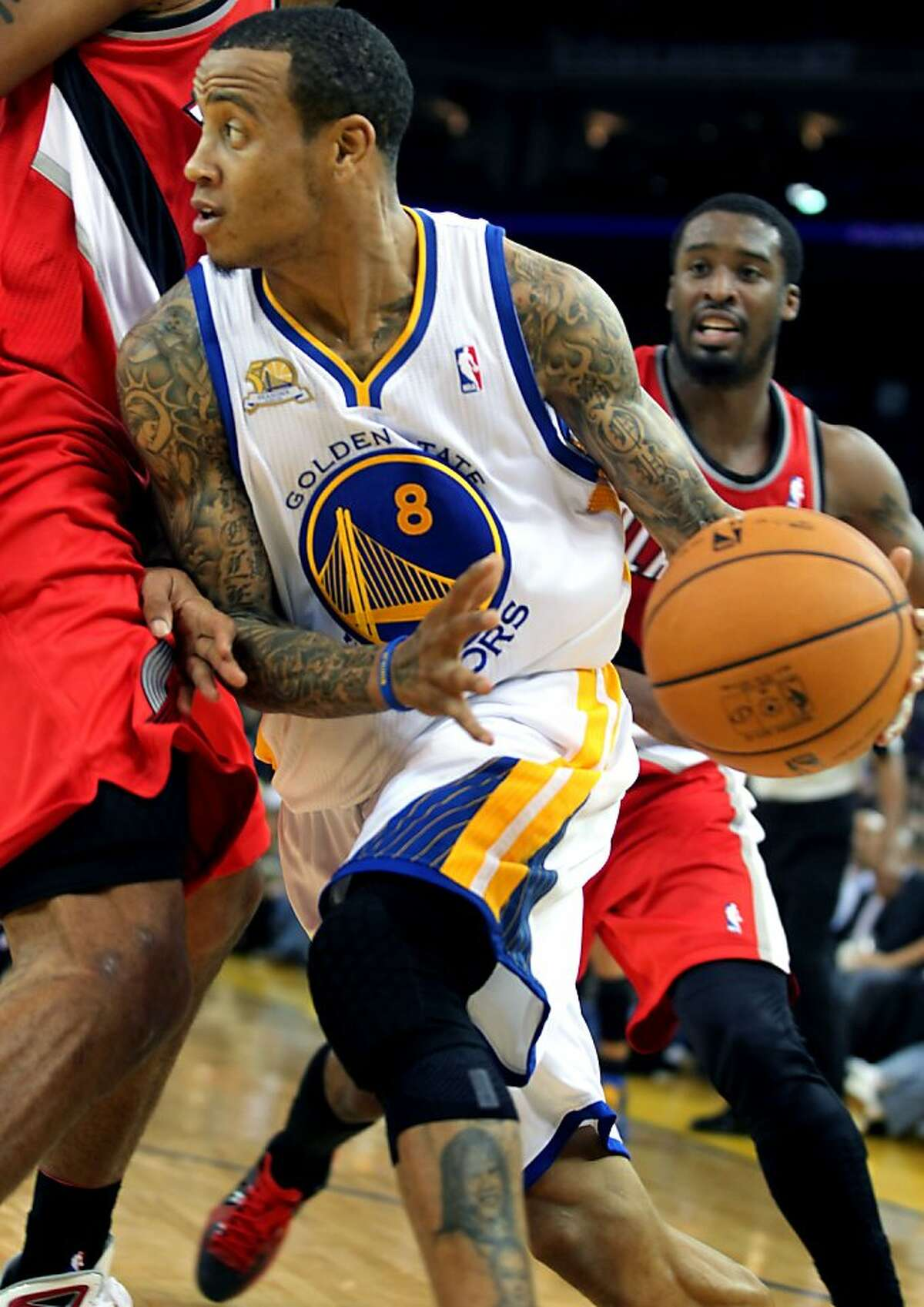 Golden State Warriors' Monta Ellis (8) drives to the basket between two Portland Trail Blazer defenders during the first half of their NBA basketball game in Oakland, Calif., Wednesday, January 25, 2012.
