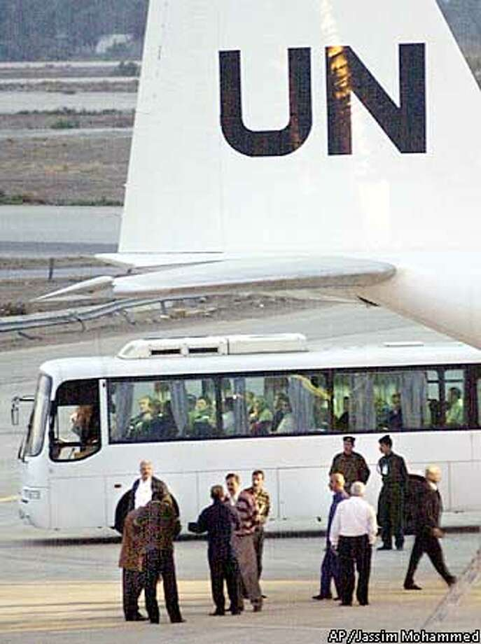 U.N. weapons inspectors sit in a bus after arriving at Saddam Airport in Baghdad, Iraq, Monday Nov. 25, 2002. The first team of U.N. inspectors landed in Iraq on Monday afternoon to take up the hunt for chemical, biological or nuclear arms programs. (AP Photo/Jassim Mohammed) Photo: JASSIM MOHAMMED