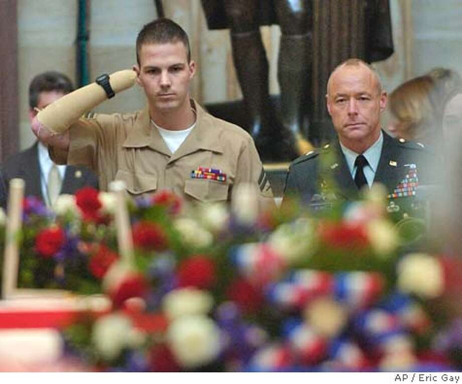 Cpl. James E. Wright, left, salutes the casket of former U.S. President in the Capitol Rotunda Thursday, June 10, 2004 in Washington, DC. Wright lost his arm during the war in Iraq. The officer on the right is unidentified. (AP Photo/Eric Gay) Photo: ERIC GAY