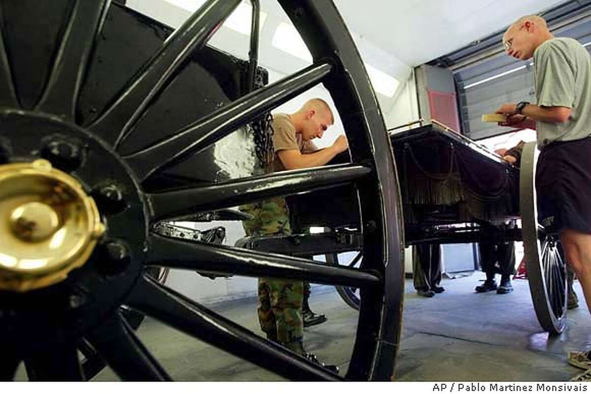 Spc. Jason Dye, left, and Sgt. Robert Dodge, right, of the Old Guard Regimental Motor Pool at Fort Myer, adjacent to Arlington National Cemetery, work on the Caisson that will be used in the funeral services for former President Ronald Reagan, before it is disassemble and repainted Monday, June 7, 2004 in Arlington, Va. (AP Photo/Pablo Martinez Monsivais) At Fort Myer near Arlington National Cemetery in Arlington, Va., Spc. Jason Dye (left) and Sgt. Robert Dodge work on the caisson that will carry Ronald Reagan's coffin.