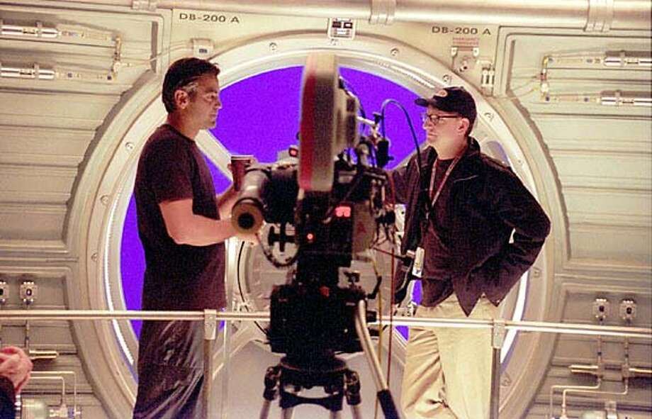 """George Clooney (left) and director Steven Soderbergh on the set of """"Solaris,'' in which Clooney visits a space station and encounters strange phenomena."""