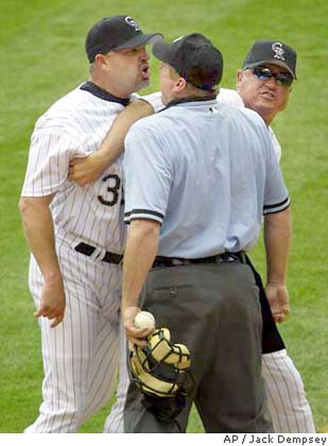 Colorado Rockies manager Clint Hurdle , right, tries to hold back relief pitcher Steve Reed, left, as he argues with home plate umpire Bruce Dreckman over a hit batsman call on San Francisco Giants A.J. Pierzynski during the eighth inning at Coors Field in Denver, Sunday, June 6, 2004. Reed was ejected from the game. (AP Photo/Jack Dempsey)