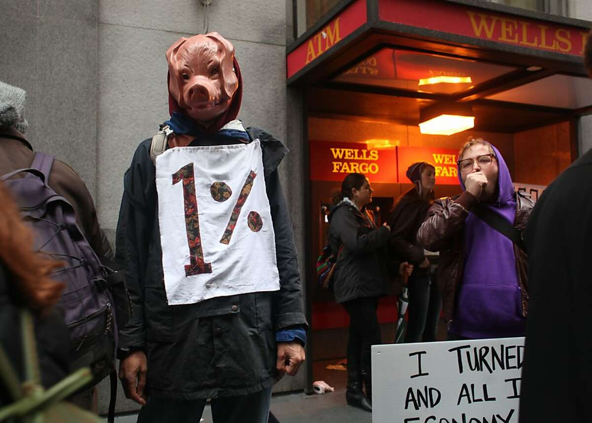 Wearing a pig mask in front of Wells Fargo Bank, Oliver Bock, a stay at home dad, of Palo Alto, Calif., joins the Occupy SF day of action on Friday January 20, 2012 in San Francisco Calif.