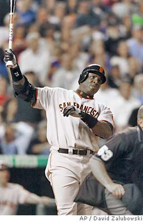 As home plate umpire Larry Pincino, front (partially obscured), checks to see if the ball stays fair, San Francisco Giants' Barry Bonds holds up his bat and watches the flight of his two-run home run on a pitch from Colorado Rockies relief pitcher Jeff Fassero in the fifth inning in Denver on Friday, June 4, 2004. (AP Photo/David Zalubowski) Photo: DAVID ZALUBOWSKI