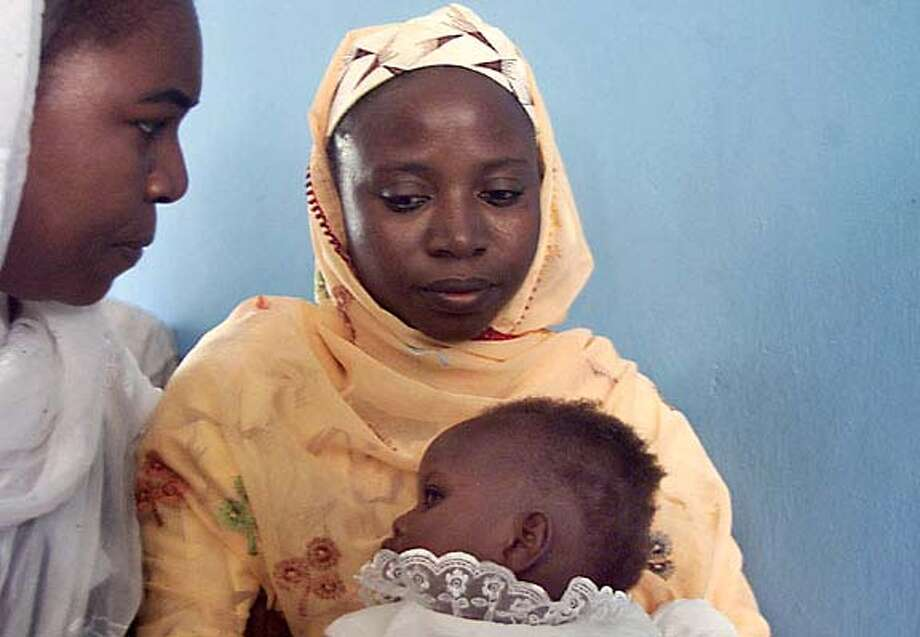 Lawyer Hauwa Ibrahim, left, reassures Amina Lawal, center, holding her baby Wasila at the court in Katsina, Nigeria, Thursday, Sept. 25, 2003. Amina a 32-year-old single mother, was sentenced in March 2002 to be buried up to her neck in sand and then stoned for giving birth to a child out of wedlock. An Islamic court Thursday overturned the conviction. (AP Photo/Str) cat w/NIGERIA26 Photo: STR