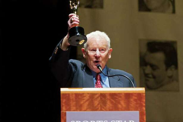 Bob Robertson, the voice of the Washington State Cougars football team for 44 years, raises the Keith Jackson Award he received at the 77th Annual Sports Star of the Year, presented by ROOT SPORTS, at Benaroya Hall in Seattle Wednesday, Jan. 25, 2012. The evening honors Northwest sports stars, carrying on an annual tradition started by Seattle Post-Intelligencer sports editor Royal Brougham in 1936.