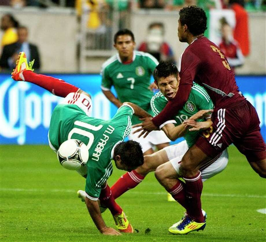 Mexico's Marcos Fabian (10) flips after colliding with Oribe Peralta (18) and Venezuela 's Carlos Salazar (3) during the first half of a friendly soccer match, Wednesday, Jan. 25, 2012, in Houston. (AP Photo/Dave Einsel) Photo: Dave Einsel, Associated Press / FR43584 AP
