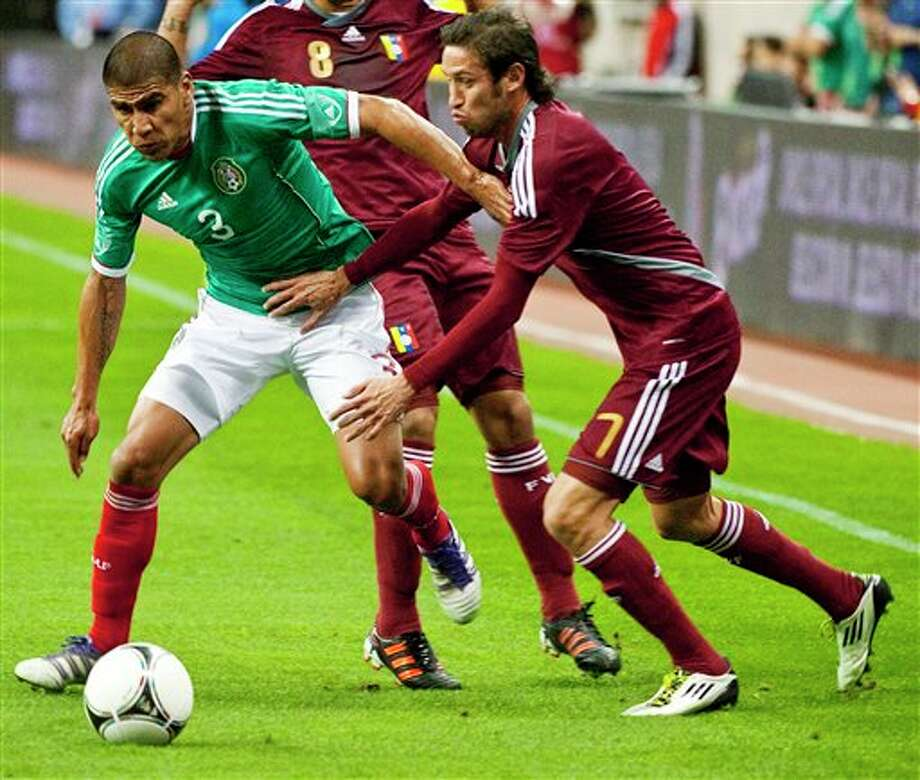 Mexico's Carlos Salcido (3) pushes away from Venezuela's Edgar Greco (7) during the first half of a friendly soccer match, Wednesday, Jan. 25, 2012, in Houston. (AP Photo/Dave Einsel) Photo: Dave Einsel, Associated Press / FR43584 AP
