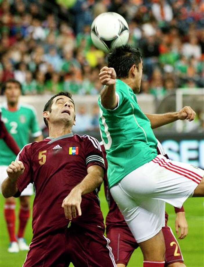 Venezuela's Micky Mea Vitali (5) defends against Mexico's Marcos Fabian, right, during the first half of a friendly soccer match, Wednesday, Jan. 25, 2012, in Houston. (AP Photo/Dave Einsel) Photo: Dave Einsel, Associated Press / FR43584 AP