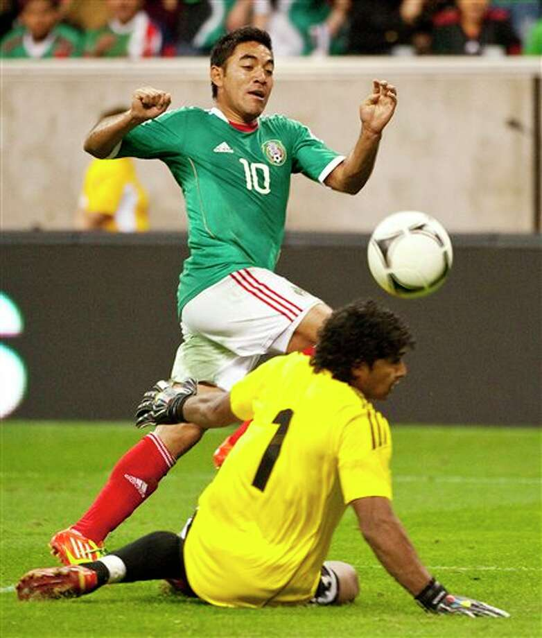 Mexico's Marcos Fabian (10) chips the ball by Venezuela goalie Leonardo Morales (1) to set up a goal by Rafael Marquez Lugo during the second half of a friendly soccer match, Wednesday, Jan. 25, 2012, in Houston. Mexico won 3-1. (AP Photo/Dave Einsel) Photo: Dave Einsel, Associated Press / FR43584 AP