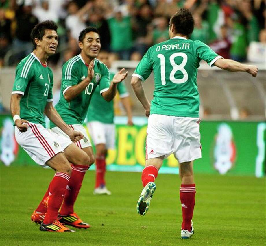Mexico's Jesus Molina (21) and Marcos Fabian (10) congratulate Oribe Peralta (18) after his goal during the second half of a friendly soccer match against Venezuela, Wednesday, Jan. 25, 2012, in Houston. Mexico won 3-1. (AP Photo/Dave Einsel) Photo: Dave Einsel, Associated Press / FR43584 AP