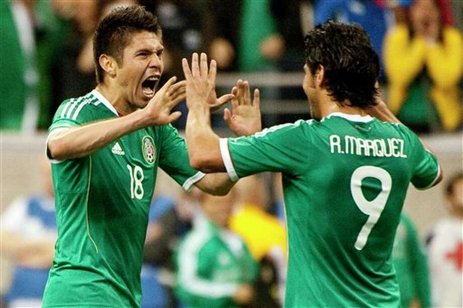 Mexico's Oribe Peralta (18) celebrates with Rafael Marquez Lugo (9) after scoring a goal during the second half of a friendly soccer match against Venezuela, Wednesday, Jan. 25, 2012, in Houston. Mexico won 3-1. (AP Photo/Dave Einsel) Photo: Dave Einsel, Associated Press / FR43584 AP
