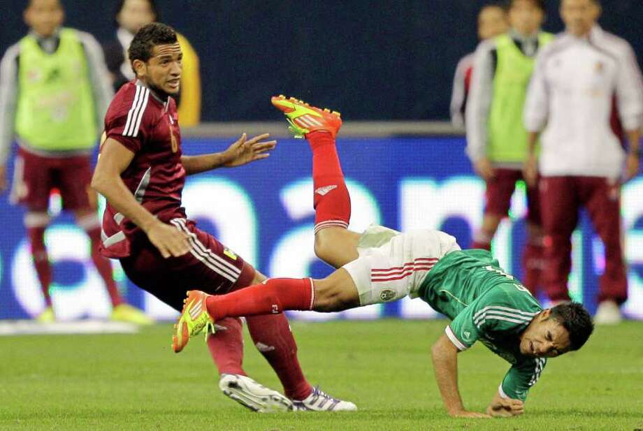 HOUSTON - JANUARY 25:  Agnel Flores #6, left, of Venezuela collides with Marcos Fabian #10 of Mexico during the international friendly between Mexico and Venezuela at Reliant Stadium on January 25, 2012 in Houston, Texas. Mexico defeated Venezuela 3-1. Photo: Bob Levey, Getty Images / 2012 Getty Images