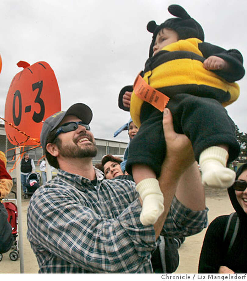 Event on 10/16/04 in Half Moon Bay.  Luke Morrissey, from Half Moon Bay, lifts his son Keaghan Morrissey, 4 1/2 months old, in the air during the judging of the costume contest. Keaghan is dressed as a bumble bee.  The Half Moon Bay Art and Pumpkin Festival, which included a costume contest, Parade, Pie Eating Contest, Pumpkin Run/Walk and Pumpkin Carving contest. The festival continues through 5pm on Sunday.  Liz Mangelsdorf / The Chronicle Photo: Liz Mangelsdorf