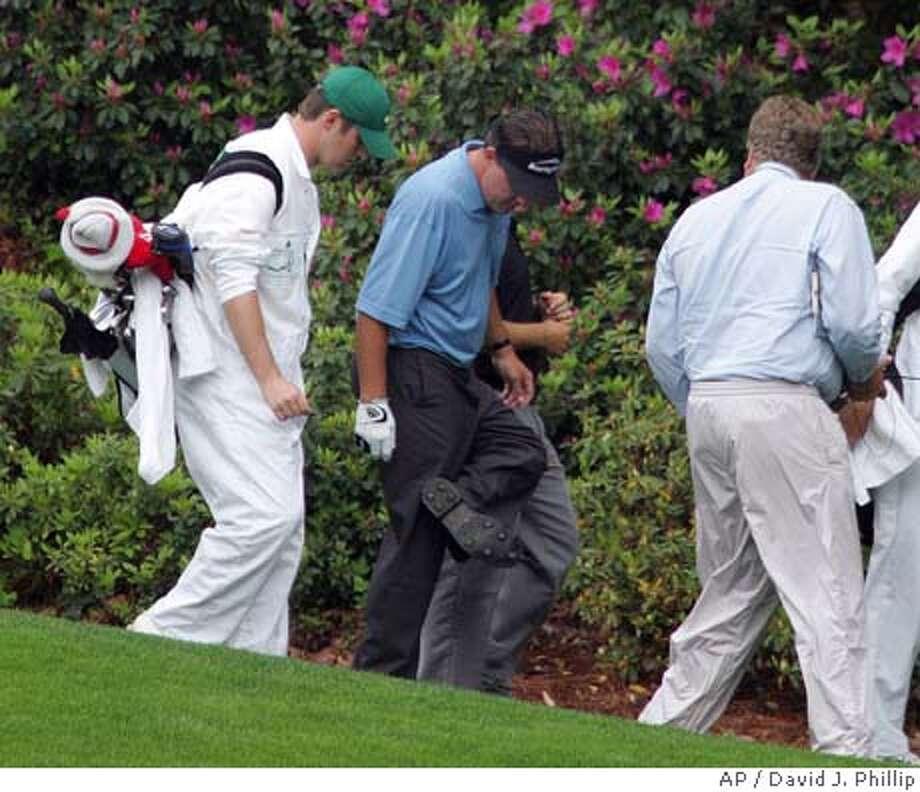 Phil Mickelson looks at the bottom of his shoes on the 13th hole after a course official informed him that playing partner Vijay Singh thought that his spikes were too long during the first round of the rain-delayed 2005 Masters at the Augusta National Golf Club in Augusta, Ga., Friday, April 8, 2005. (AP Photo/David J. Phillip) Photo: DAVID J. PHILLIP