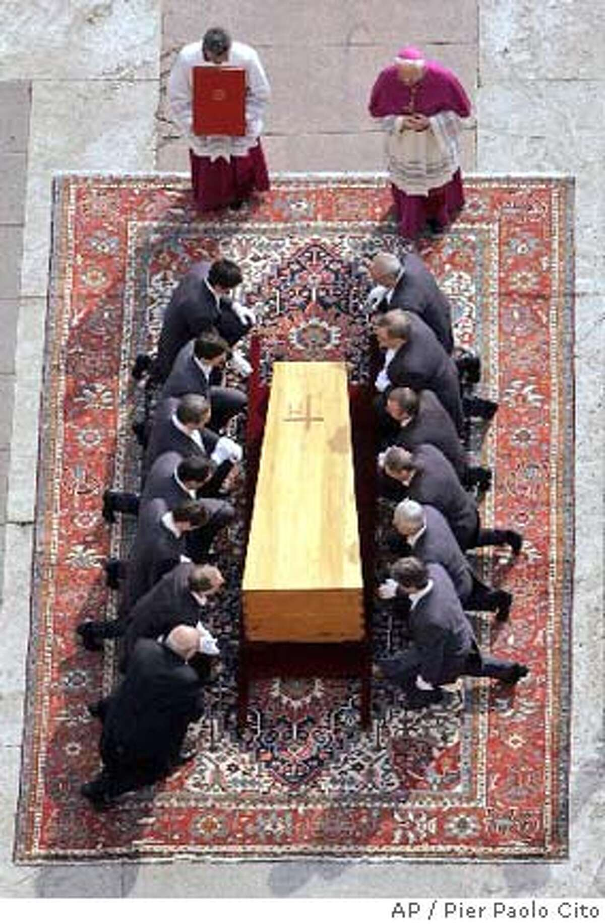 Pallbearers kneel by the coffin of Pope John Paul II during the funerals at the Vatican, Friday, April 8, 2005. Tens of thousands of people jammed St. Peter's Square to say a final farewell to Pope John Paul II in the presence of kings, queens, presidents and prime ministers for a funeral capping one of the largest religious gatherings in the West in modern times. AP Photo / Pier Paolo Cito