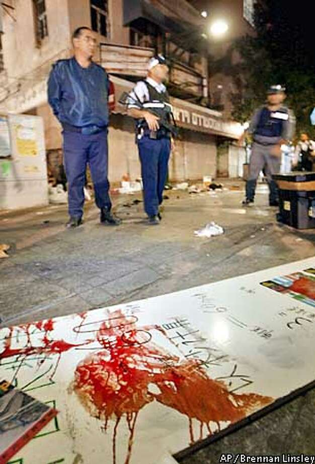 Israeli investigators stand near a sign stained with blood, at the scene of a double suicide bombing, in Tel Aviv, Israel, Sunday, Jan. 5, 2003. The two attacks, which occured a block away from each other, left at least 19 dead, and dozens injured. (AP Photo/Brennan Linsley) Photo: BRENNAN LINSLEY