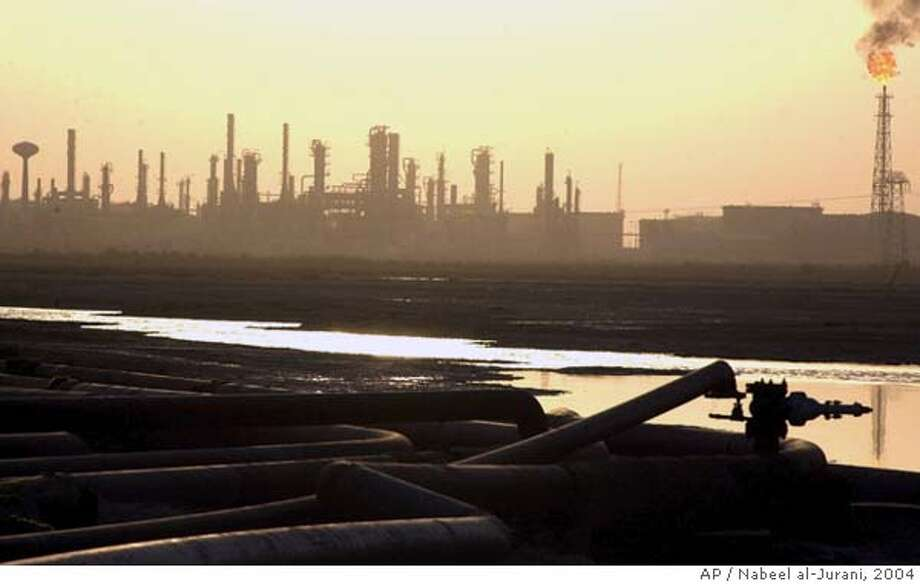 An oil refinery 30 kilometers south of Basra, Iraq, operates Friday June 18, 2004. Full crude oil exports from southern Iraq are expected by the end of next week, but could come as early as Wednesday, coalition officials said Friday as crews have been rushing to complete repairs on a major export pipeline system damaged by insurgents this week. (AP Photo/Nabeel al-Jurani) Ran on: 06-30-2004  A worker walks among pipes at the Baba Gurgur oil field in Kirkuk, northern Iraq. Photo: NABEEL AL-JURANI