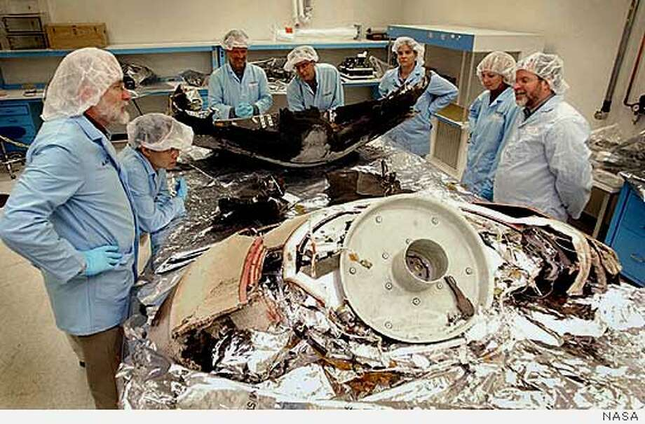 Scientists examine pieces of the Genesis space capsule at Lockheed Martin in Denver on Oct. 4. Genesis crashed Sept. 8. NASA Photo