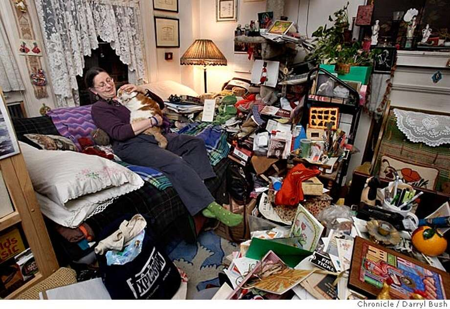 """Sandra Baker sits on a futon and plays with one of her two cats, """"Christopher,"""" in the living room of her cluttered apartment in the Tenderloin. Event on 3/31/05 in San Francisco.  Darryl Bush / The Chronicle Photo: Darryl Bush"""