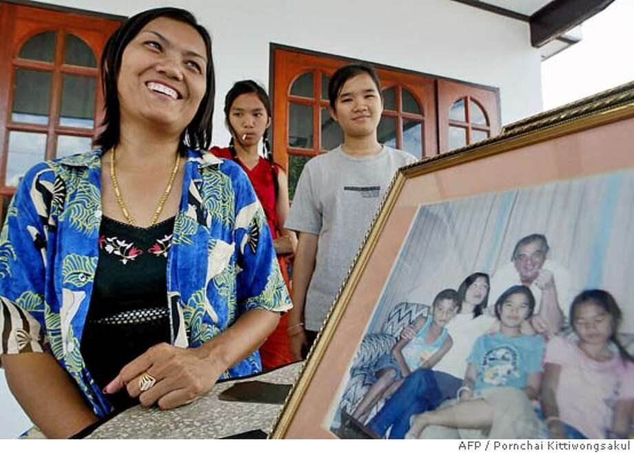 TO GO WITH AFP STORY LIFESTYLE-THAILAND-WIVES  Thai provincial official, Anthika Sarawithee (L) smiles next to a photo of her English partner John with their children at her house in Roi Et northern Thailand, 20 June 2004. Thailand's impoverished northeast is embracing the economic windfall from more than 15,000 foreign sons-in-law and attempting to end the stigma attached to women who marry men from overseas. AFP PHOTO/Pornchai KITTIWONGSAKUL Photo: PORNCHAI KITTIWONGSAKUL