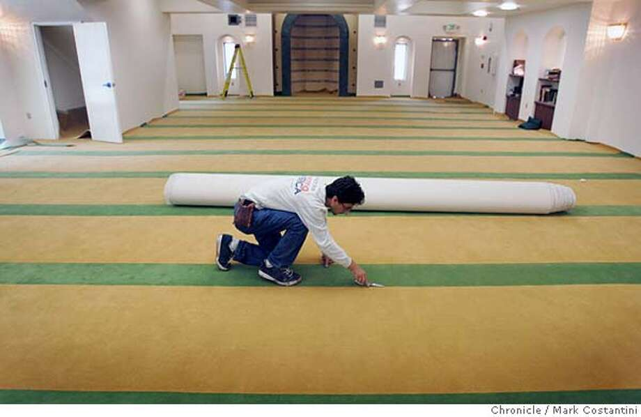 A carpet installer carefull seams the green and yellow carpet. The purpose of the striping is to establish where a worshipper should kneel for prayer.  New Mosque under construction on 31st. St. near Telegraph in Oakland. Event on 10/14/04 in Oakland  Chronicle photo by Mark Costantini. Metro#Metro#Chronicle#10/15/2004#ALL#5star##0422413717 Photo: Mark Costantini