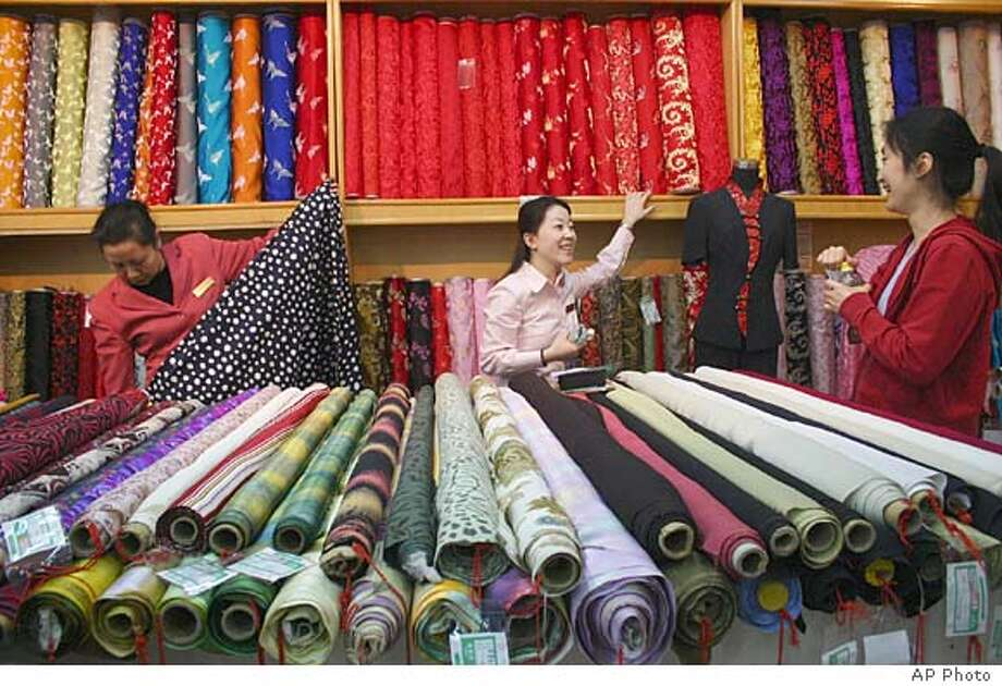 A Chinese salesclerk speaks to a customer at a textile shop in downtown Beijing Wednesday, April 6, 2005. Quotas on virtually all textile and apparel items were lifted Jan. 1 as a condition of China's new membership in the World Trade Organization. But the membership also guarantees the U.S. government can challenge some of China's trading freedoms if it can prove American markets are being harmed. (AP Photo)