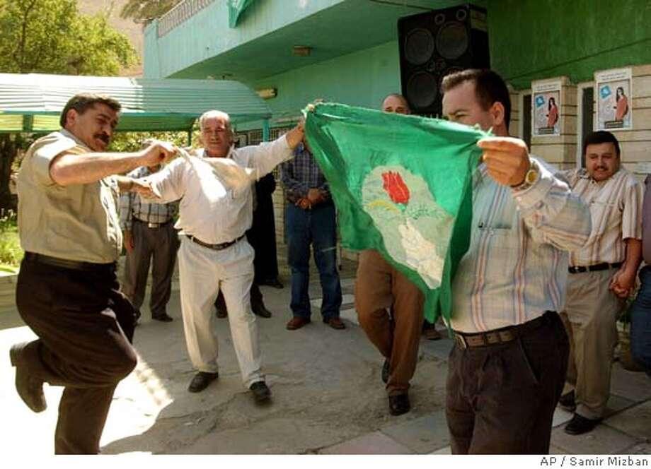 **RETRANSMITTING TO CORRECT CAPTION** Kurdish Iraqi men celebrate the election of new Iraqi President Jalal Talabani at the Patriotic Union of Kurdistan, P.U.K., headquarters in Baghdad, Iraq, Wednesday, April 6, 2005. The man at right is holding the P.U.K. flag. (AP Photo/Samir Mizban) RETRANSMITTING TO CORRECT CAPTION Photo: SAMIR MIZBAN