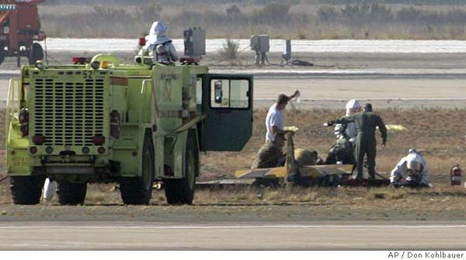 """Military rescue personnel work at the site of the crash of Sean deRosier's """"Sky Rocker"""" stunt plane after it crashed at the beginning of the Miramar Air Show at Marine Corps Air Station Miramar in San Diego on Friday, Oct. 15, 2004, killing deRosier, the pilot. (AP Photo/San Diego Union-Tribune, Don Kohlbauer) Photo: DON KOHLBAUER"""