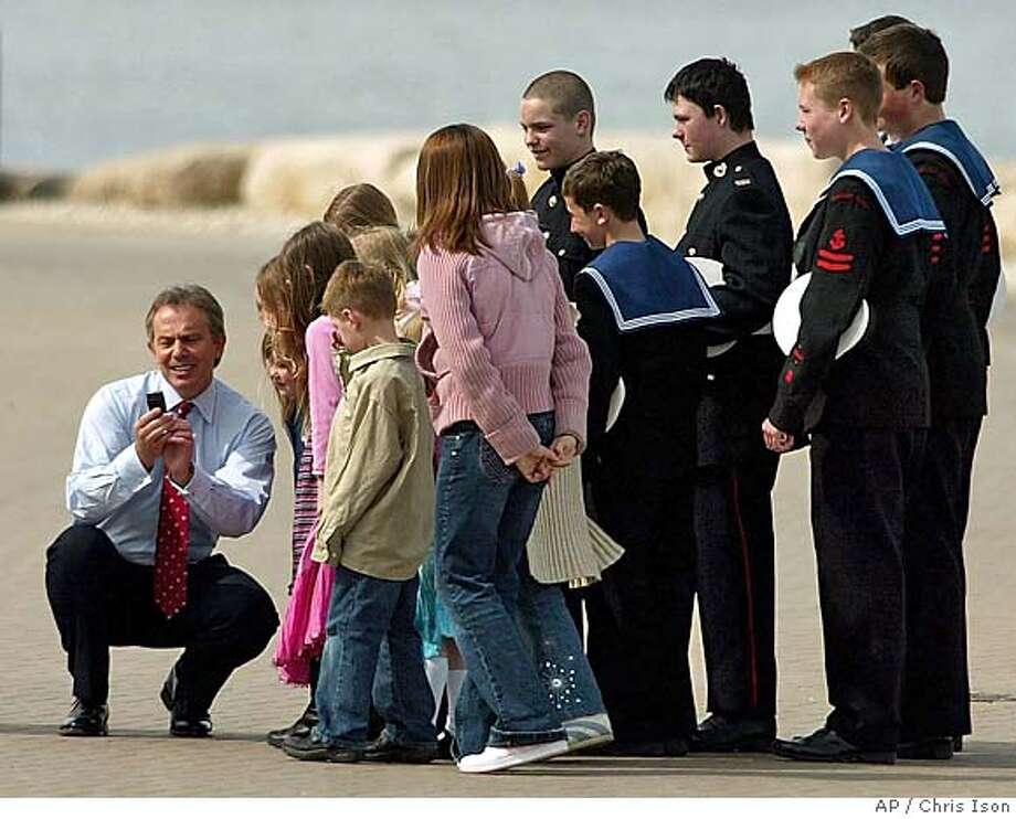 Britain's Prime Minister Tony Blair looks a at picture he took with a mobile phone camera of a group of local children and Sea Cadets at the Weymouth and Portland Sailing Academy on the Isle of Portland near Weymouth, England, Tuesday April 5, 2005. Prime Minister Blair on Tuesday called national elections on May 5, triggering a four-week campaign that will test a volatile electorate's judgment of the Iraq war. Despite lingering anger over the U.S.-led invasion, Blair's governing Labour Party is widely expected to win a third term in office, bolstered by a strong economy. (AP Photo/Chris Ison/PA) ** UNITED KINGDOM OUT ** UNITED KINGDOM OUT PHOTOGRAPH CANNOT BE STORED OR USED FOR MORE THAN 14 DAYS AFTER THE DAY OF TRANSMISSION Photo: CHRIS ISON