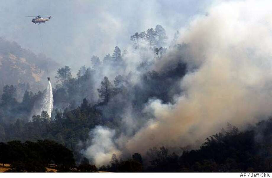 A firefighting helicopter drops water on the Rumsey Fire near Lake Berryessa, Calif., Wednesday, Oct. 13, 2004. (AP Photo/Jeff Chiu) Metro#Metro#Chronicle#10/14/2004#ALL#5star##0422411762 Photo: JEFF CHIU