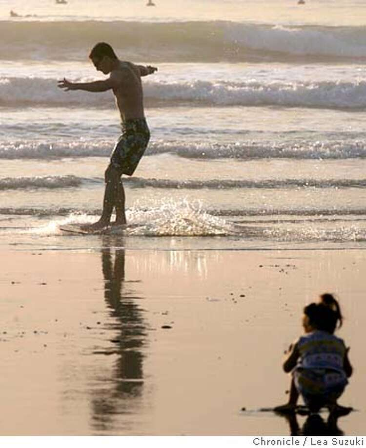weather.jpg  Oliver Eldredge of San Francisco takes one of his first attempts on a skimboard out on Ocean Beach enjoying the last of a day of hot weather. In foreground: Eva Lani Dudum, 2, of San Francisco, plays in the sand. She was enjoying the beach with her mother and waiting for her father who was surfing. Photo taken on 10/13/04 in San Francisco, CA.  Lea Suzuki/ San Francisco Chronicle MANDATORY CREDIT FOR PHOTOG AND SF CHRONICLE/ -MAGS OUT Metro#Metro#Chronicle#10/14/2004#ALL#5star##0422411668 Photo: Lea Suzuki
