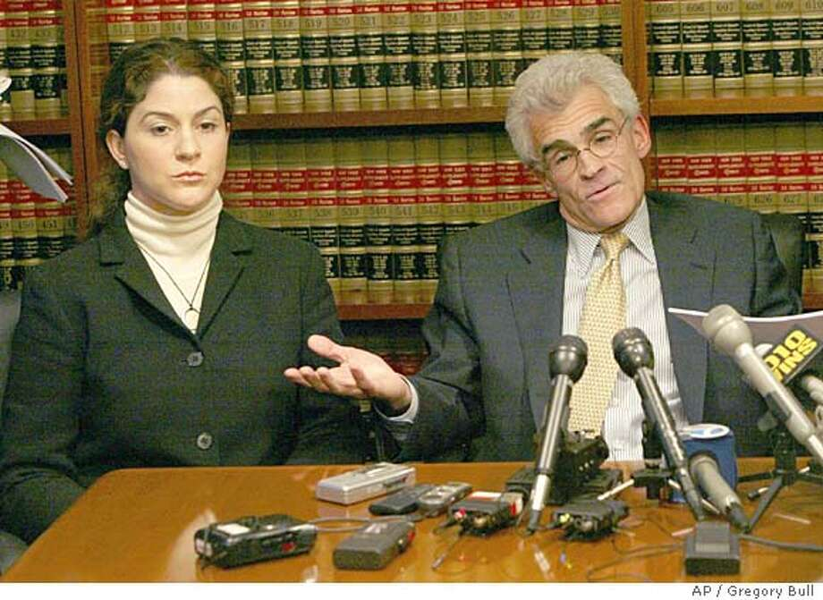 ** CAPTION CORRECTION, DELETES INCORRECT REFERENCE TO COUNTERSUIT, FOX FILED ITS SUIT FIRST ** Andrea Mackris, left, looks on as her lawyer Benedict Morelli, right, speaks at a news conference in New York, Wednesday, Oct. 13, 2004. Mackris, A Fox News Channel producer, sued Bill O'Reilly for sexual harassment Wednesday, alleging her boss had phone sex with her against her wishes three times. Fox filed a claim of its own, saying the complaint was a politically motivated extortion attempt. (AP Photo/Gregory Bull) Nation#MainNews#Chronicle#10/14/2004#ALL#5star##0422411501 Photo: GREGORY BULL