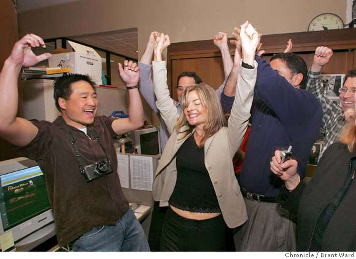 Deanne Fitzmaurice celebrates as she is named the Pulitzer Prize winner for Feature Photography Monday. She is surrounded by editors around the Photography Editor desk. Brant Ward 4/5/05