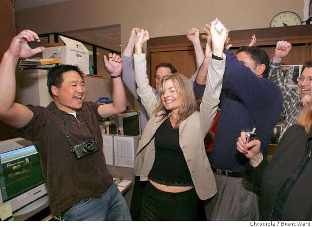 Deanne Fitzmaurice celebrates as she is named the Pulitzer Prize winner for Feature Photography Monday. She is surrounded by editors around the Photography Editor desk. Brant Ward 4/5/05 Photo: Brant Ward