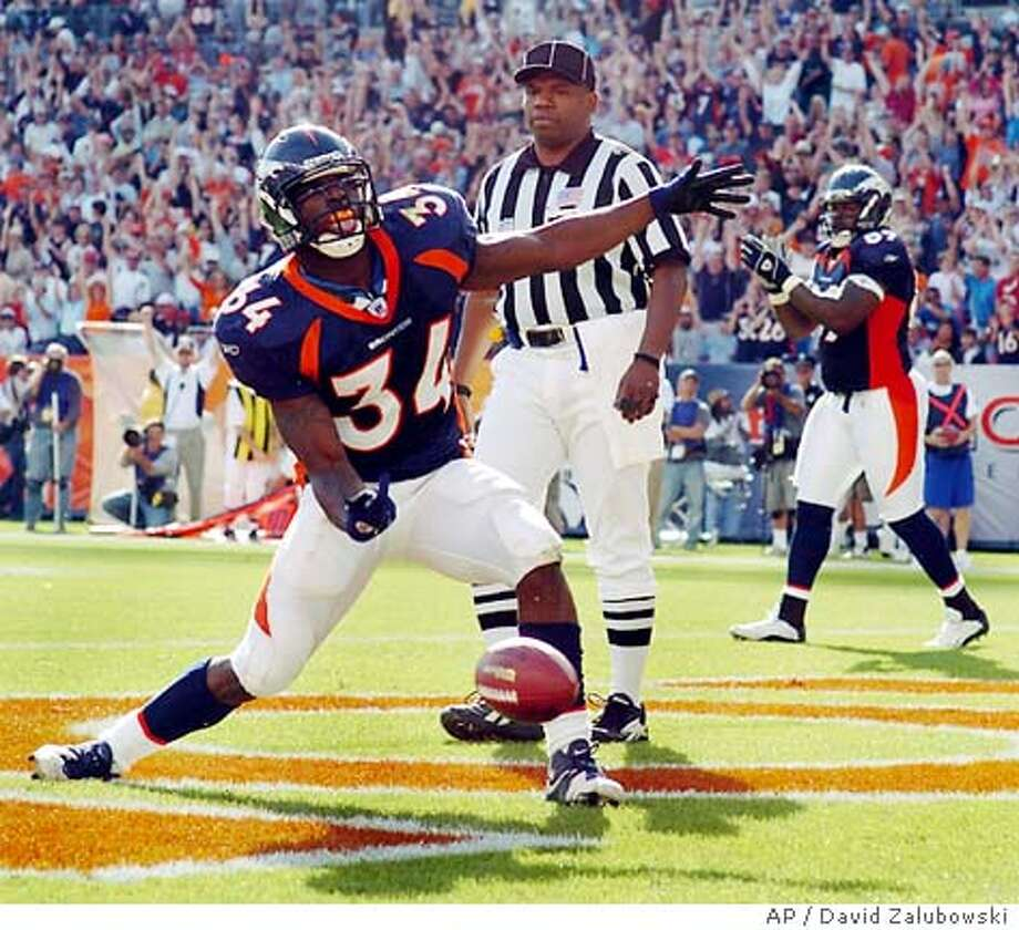 Denver Broncos running back Reuben Droughns (34) celebrates his 5-yard touchdown catch against the Carolina Panthers in the second quarter in Denver, Sunday, Oct. 10, 2004. Umpire Undrey Wash watches in the background. (AP Photo/David Zalubowski) Photo: DAVID ZALUBOWSKI