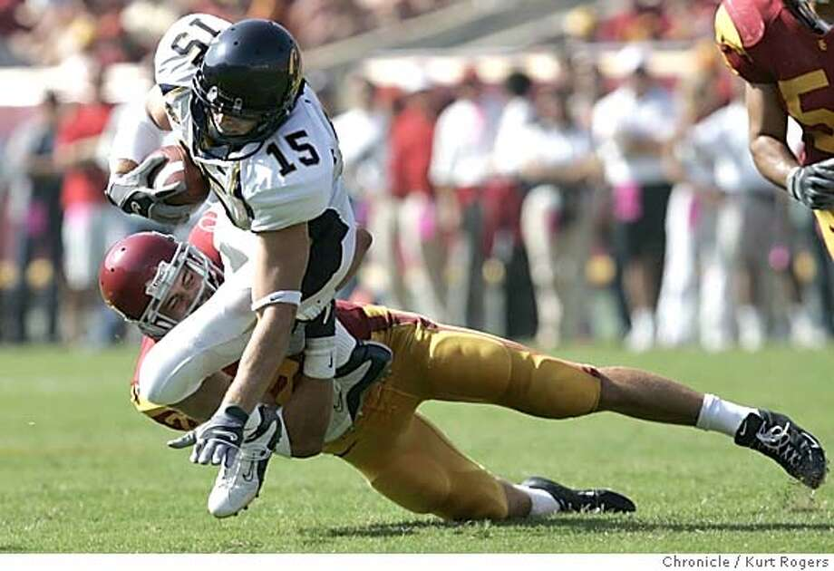 Cals Chase Lyman is tripped up byScott Ware. in the Third Quarter.  The University of California Berkeley Golden Bears vs the University of Southern California Trojans at the Los Angeles Memorial Coliseum.  CAL_407_kr.JPG 10/9/04 in Los Angeles,CA.  KURT ROGERS/THE CHRONICLE Ran on: 10-11-2004 Ran on: 10-11-2004 MANDATORY CREDIT FOR PHOTOG AND SF CHRONICLE/ -MAGS OUT Sports#Sports#Chronicle#10/12/2004#ALL#5star##0422404163 Photo: KURT ROGERS