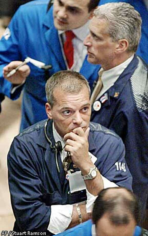 Albert Young of Olde Discount Corp. has his hand to his mouth as he watches the ticker on the floor of the New York Stock Exchange, Friday, October 4, 2002. More mixed economic news and earnings warnings sent stocks tumbling as investors decided yet again they were better off staying away from the market. The Dow Jones fell 188 points to hit a 5 year low of 7528.4. (AP Photo /Stuart Ramson) Photo: STUART RAMSON