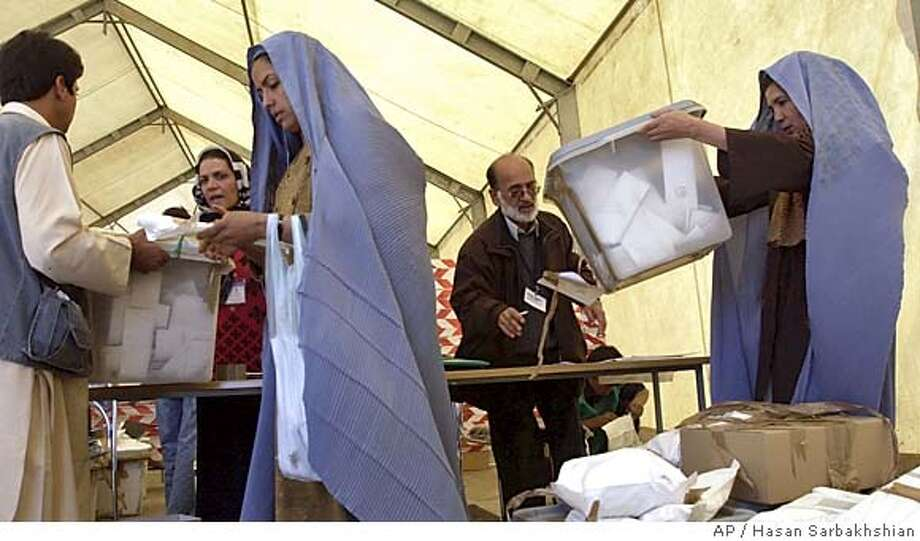 Afghan veiled election staff give ballot boxes to U.N. officially before ballot counting at a U.N. office at Herat's airport Sunday, Oct. 10, 2004, a day after Afghanistan's first-ever direct presidential election. (AP Photo/Hasan Sarbakhshian) Photo: HASAN SARBAKHSHIAN