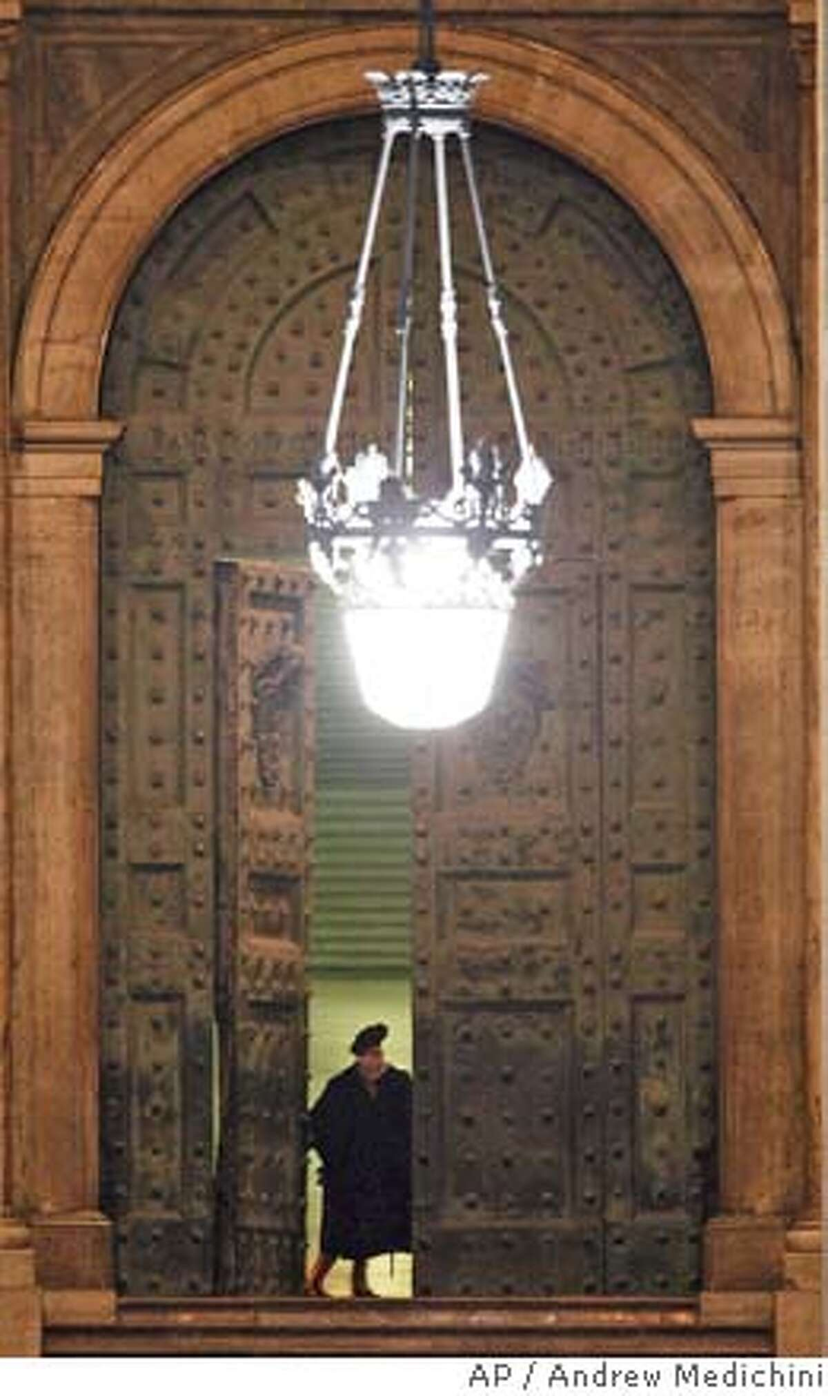 A Swiss guard closes the Bronze Door in St. Peter's Square at the Vatican, Saturday April 2, 2005, where the pontiff's life appeared to be slipping away showing the first signs of losing consciousness. (AP Photo/Andrew Medichini)