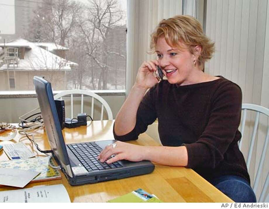 """Emily O'Brien talks with a client on her cell phone as she works from her home on a snowy Wednesday, Feb. 11, 2004, in Denver.About 60,000 people have """"cut the cord"""" by moving a home or office telephone number to a cell phone since new federal rules took effect in late November. (AP Photo/Ed Andrieski) Emily O'Brien talks with a client on her cell phone as she works from her home in Denver. Ran on: 10-10-2004  Emily O'Brien talks with a client as she works from her home in Denver. The growing use of cell phones is turning out to be a worrisome problem for political pollsters. Photo: ED ANDRIESKI"""