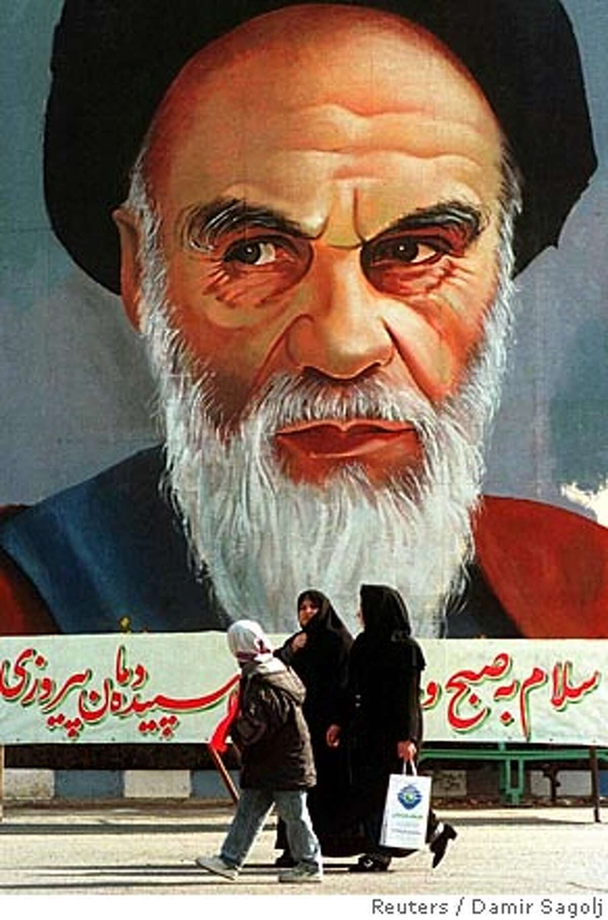 TEH04:IRAN-REVOLUTION:TEHRAN,8FEB99 - Iranian women pass by a billboard showing the late founder of the Islamic revolution Ayatollah Khomeini in the centre of Tehran February 8. Iranians will mark the 20th anniversary of the Islamic revolution next week. ds/Photo by Damir Sagolj REUTERS 9R BookReview#BookReview#Chronicle#04-03-2005#ALL#2star#e1#422008658