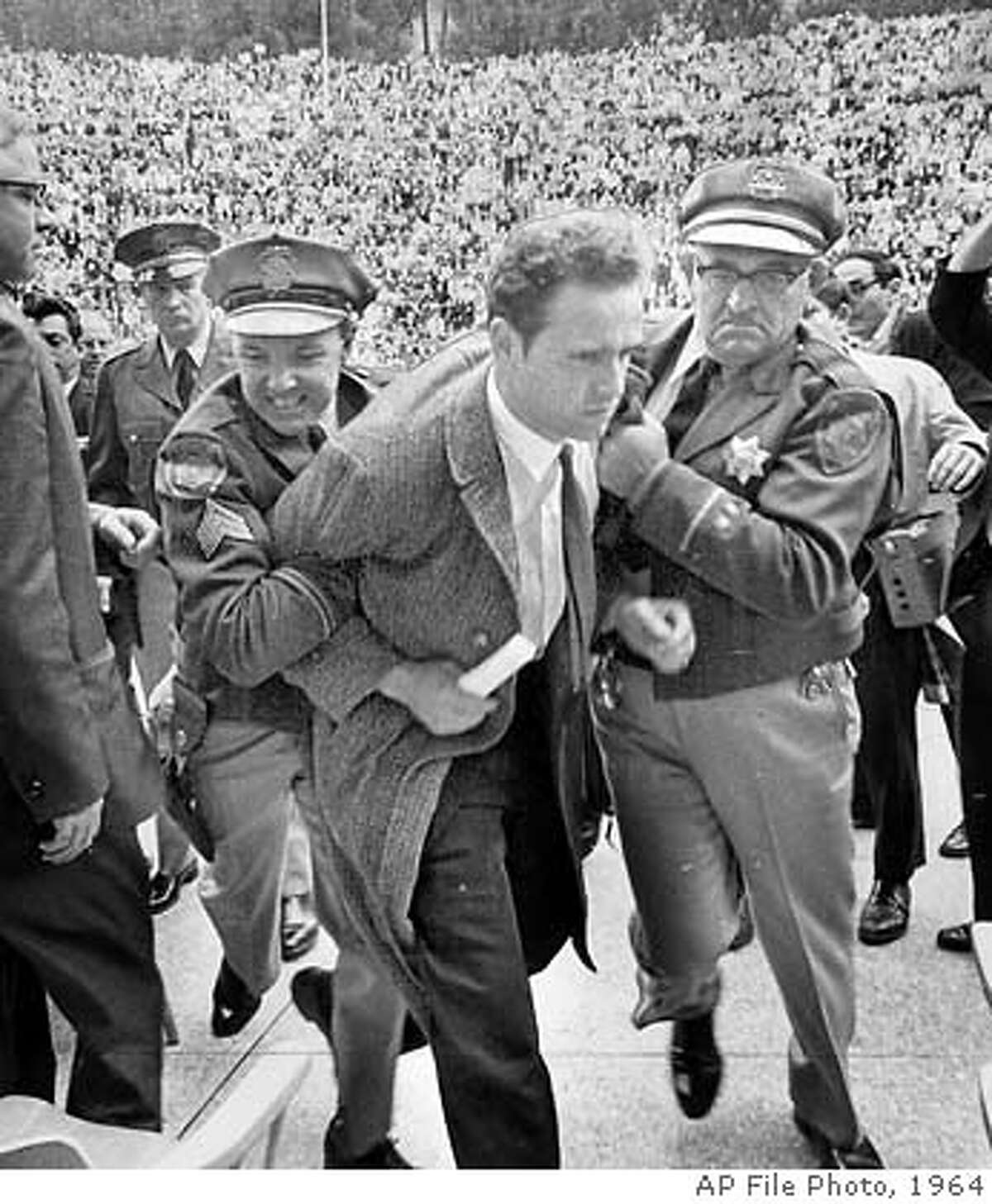 century23/b/07DEC64/SC/AP MARIO SAVIO AT THE UNIVERSITY OF CALIFORNIA CAMPUS RESTRAINED BY POLICE WHEN HE ATTEMPTED TO SPEAK FOLLOWING THE APPEARANCE OF UNIVERSITY PRESIDENT CLARK KERR. CAT