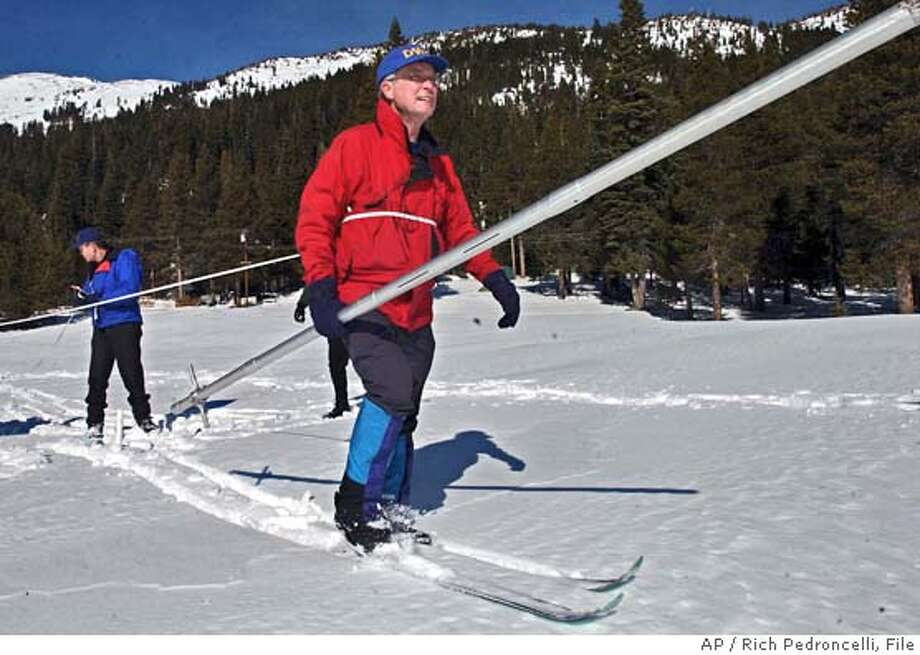 ** ADVANCE FOR SUNDAY APRIL 3 - FILE ** Hydrologist Frank Gehrke carries a snow depth pole after measuring a snowpack average of 156 precent, during a Department of Water Resources snow survey near Echo Summitt, Calif., Feb. 1, 2005. A dry, warm winter across the Northwest has fire managers and forecasters holding their breath. In the Southwest, it's the opposite. So much rain has fallen in Southern California and Las Vegas that residents there make jokes about living in Seattle. People in the Sierra Nevada are still digging out from snowstorms. (AP Photo/Rich Pedroncelli, File) Photo: RICH PEDRONCELLI
