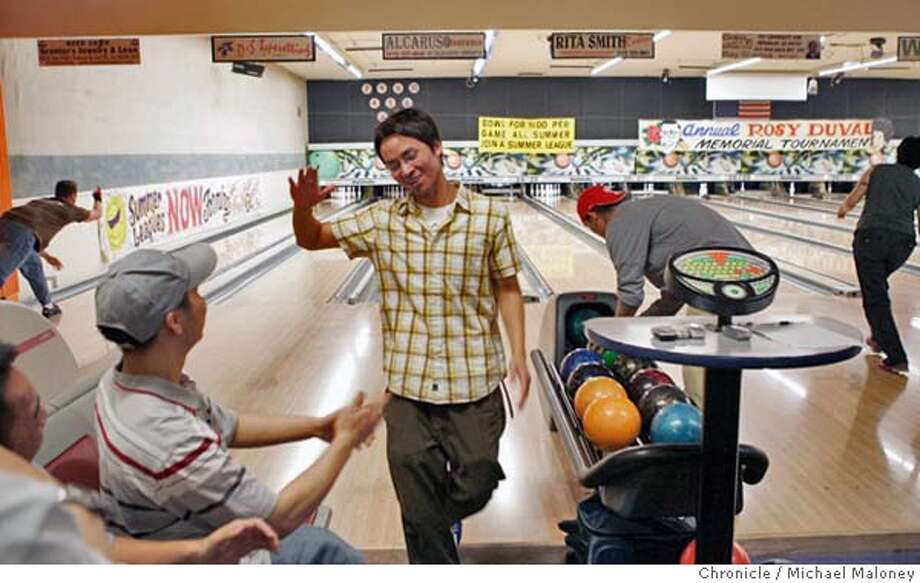 LIFE31_070_MJM.jpg  Hoa Huynh, standing, reacts to his strike. At left with hat is Sarn Lin Saechao, both are 21 and from Richmond.  Albany Bowl is packed Monday & Tuesday nights, when they charge only $1.50 a game (instead of $4.50). At times there is a two hour wait just to play. The place is an institution, been in Albany since 1949, and what's surprising is that the place is packed with people in their 20s and 30s, who don't find bowling too old-fashioned at all.  Photo by Michael Maloney / San Francisco Chronicle MANDATORY CREDIT FOR PHOTOG AND SF CHRONICLE/ -MAGS OUT Photo: Michael Maloney